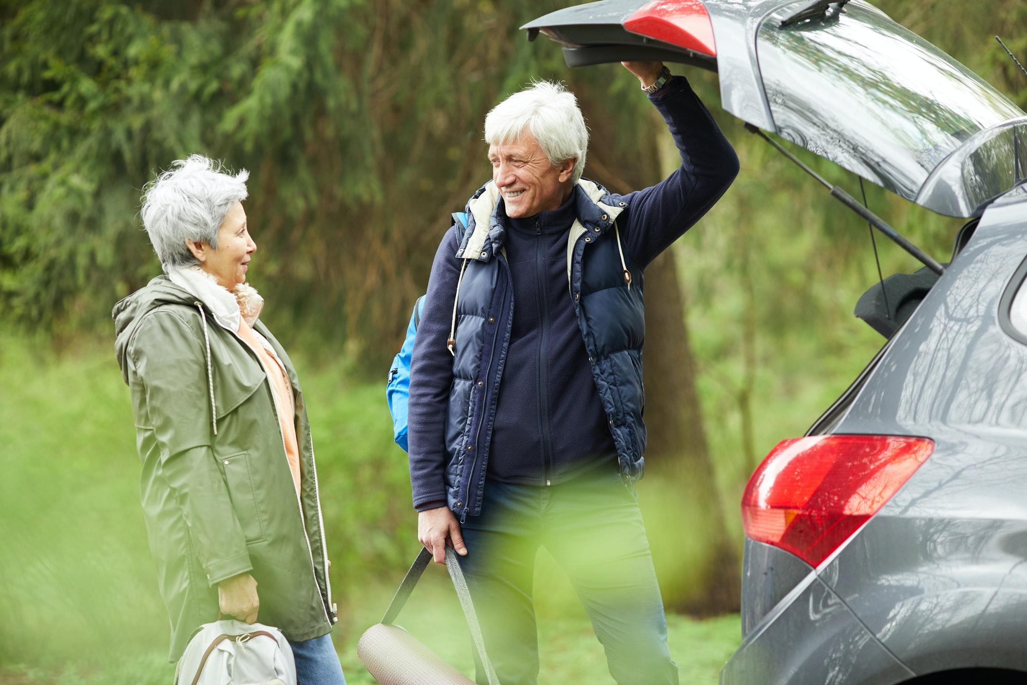 Active Senior Couple by Car